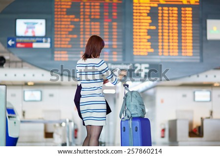 Young female passenger at the airport, looking at the flight information board - stock photo