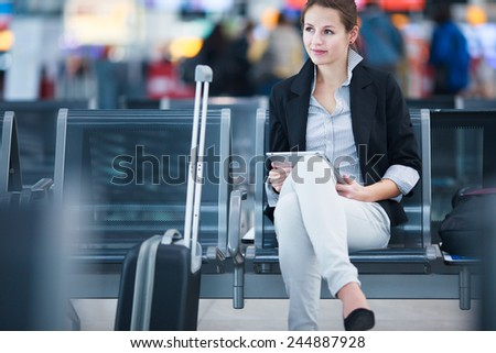 Young female passenger at the airport, using her tablet computer while waiting for her flight (color toned image) - stock photo