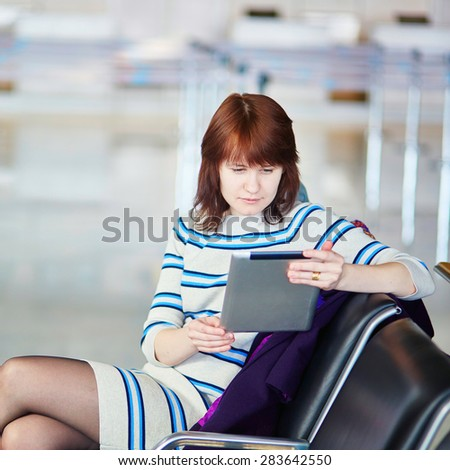 Young female passenger at the airport, using her tablet computer while waiting for her flight