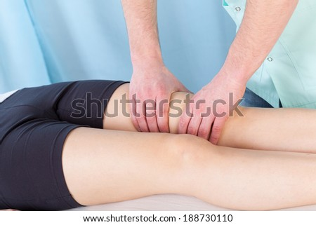 Young female patient getting therapeutic leg massage - stock photo