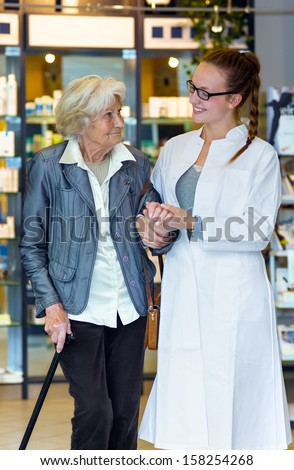 Young female pharmacist gently holding and supporting senior female patient in the pharmacy