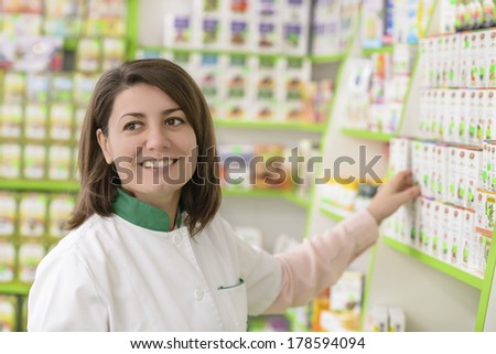 Young female pharmacist in a drugstore - stock photo