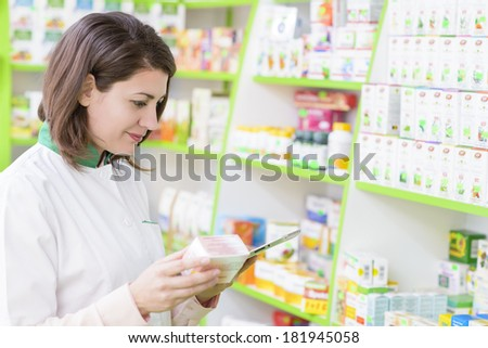 Young female pharmacist in a drugstore working on a tablet pc - stock photo