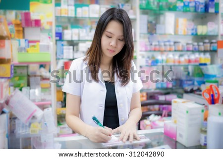 Young female pharmacist picking medicine and drugs from shelves in the drugstore - stock photo