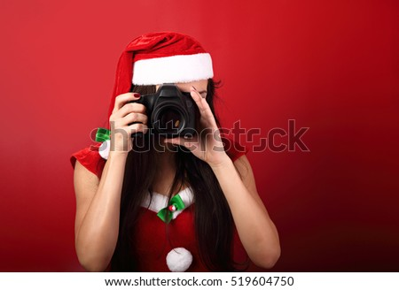 Young female photograph making the photo on red background holding the camera in santa clause clothing