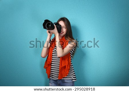 Young female photographer taking photos on blue background - stock photo