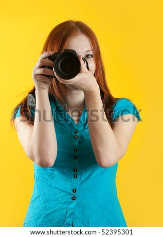 Young female photographer with camera over yellow background - stock photo