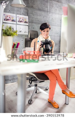 Young female photographer with professional photo camera in photo studio
