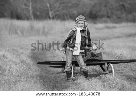 Young female pilot in a homemade airplane on a field road at sunny autumn day