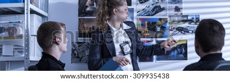 Young female police officer talking with policeman - stock photo