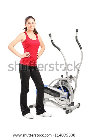 Young female posing next to a cross trainer isolated on white background