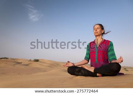 Young female practicing yoga meditation on sand dune Jaisalmer, India - stock photo