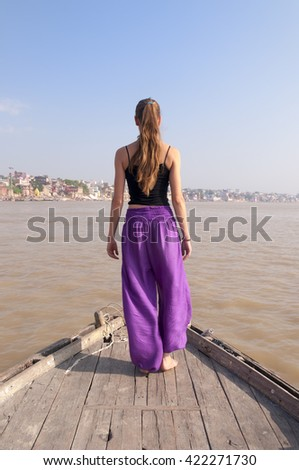 Young female practising standing yoga meditation on the boat over Ganga river, India