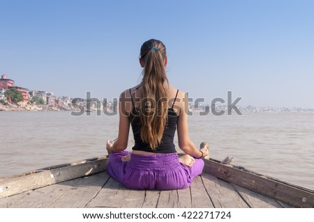 Young female practising yoga meditation on the boat over Ganga river, India - stock photo