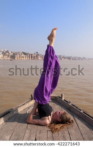 Young female practising yoga pose Sarvangasana on the boat over Ganga river, India