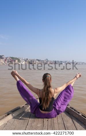 Young female practising yoga pose Upavishta konasana on the boat over Ganga river, India - stock photo