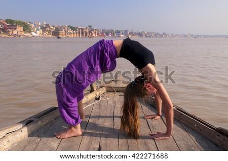 Young female practising yoga pose Urdhva Dhanurasana on the boat over Ganga river, India - stock photo