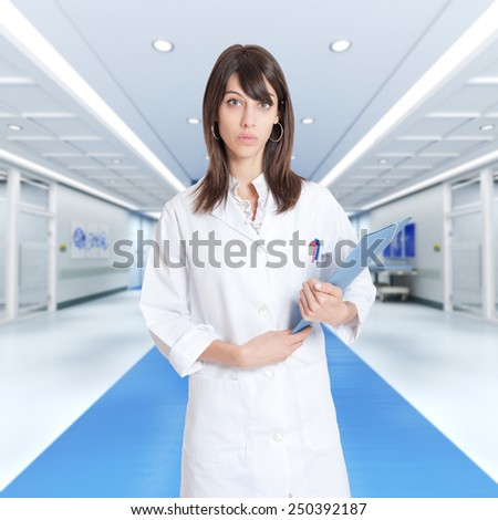 Young female professional holding a binder in a hospital corridor