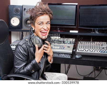 Young female professional laughing while sitting at mixing desk in recording studio