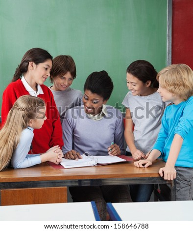 Young female professor teaching group of students at desk in classroom