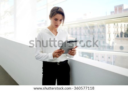 Young female proud ceo dressed in formal wear working on digital tablet while standing in modern office interior, woman entrepreneur concentrated reading electronic book on touch pad during work break - stock photo
