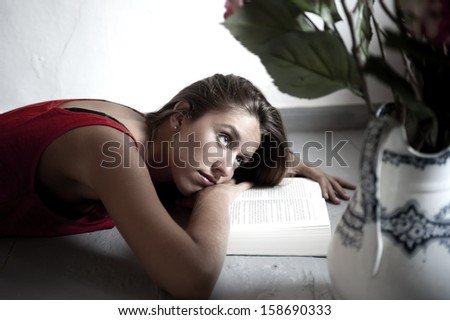 Young female reading book while lying on floor