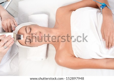 Young female receiving facial beauty treatment at beauty saloon, above view. - stock photo