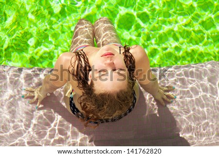 young female relax and enjoy at swimming pool. Horizontal shot, outdoors. - stock photo