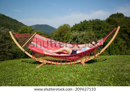 Young female relaxing in a hammock at hill top - stock photo