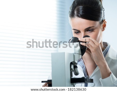 Young female researcher using microscope in the laboratory close up. - stock photo
