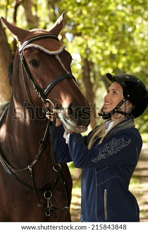Young female rider looking at horse with love, outdoor photo. - stock photo
