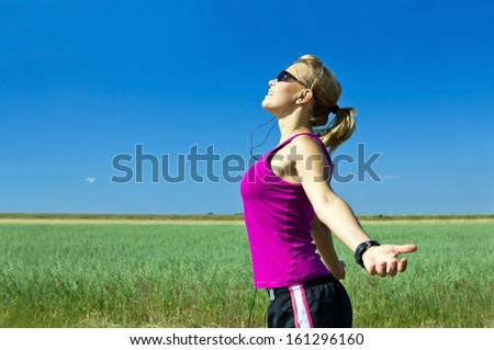 Young female runner exercising and stretching in summer nature. Happy woman running on country road, bright sunlight and colorful environment, sport and fitness - stock photo