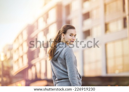 Young female runner in hoody is jogging in the city street - stock photo
