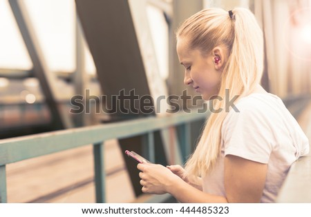 Young female runner is having break and listening to music during the run in city on a bridge