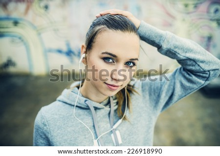 Young female runner is having break and listening to music in the street - stock photo