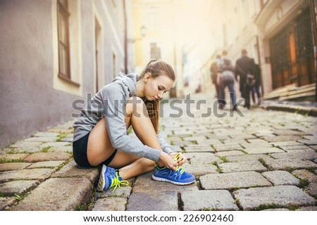Young female runner is tying her running shoes on tiled pavement in old city center - stock photo