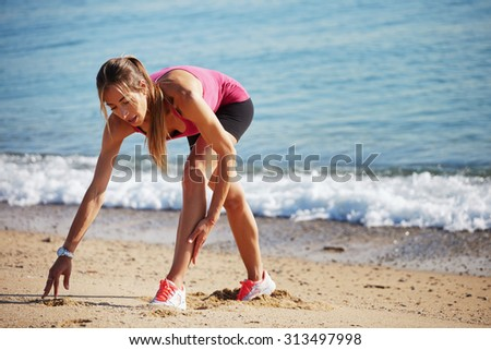 Young female runner preparing for jogging while stretching legs muscles on the background of sea waves, attractive sportswoman with beautiful figure doing an active fitness training on the beach - stock photo