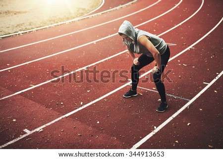 Young female runner standing on stadium and listening to music, relaxing after running