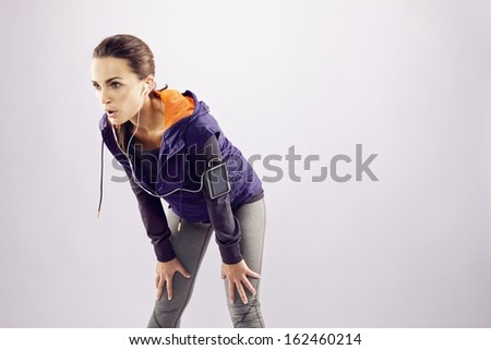 Young female  runner with hands on knees. Tired young woman resting after jogging on grey background with lots of copyspace - stock photo