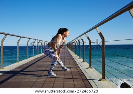 Young female runner with sexy body in sport bra and training tights warming up before workout outdoors, sporty woman stretching legs while standing on wooden jetty with ocean horizon on background - stock photo