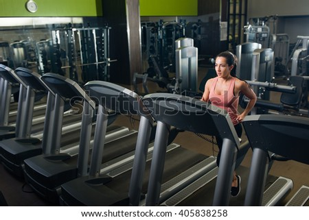 Young female running on a treadmill in a gym - stock photo