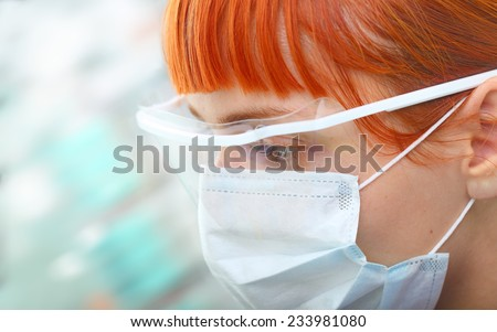Young female scientist in protective spectacles and surgical mask attentively looks in the modern laboratory  - stock photo