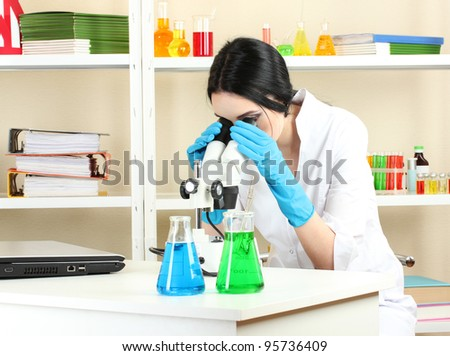 Young female scientist looking at microscope in chemistry laboratory