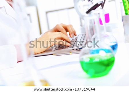 Young female scientist working with liquids in laboratory