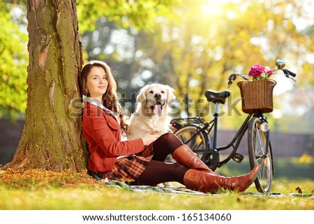 Young female sitting on a grass with her dog and looking at camera in a park - stock photo