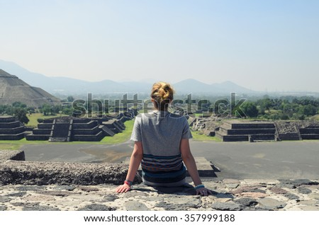 Young female sitting on top of pyramid and overlooking Teotihuacan ruins - stock photo