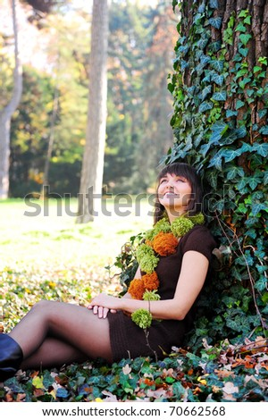 Young female sitting under a tree on grass at the park. - stock photo