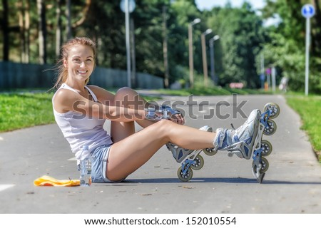 Young female skater sitting on the road and ties her rollers - stock photo