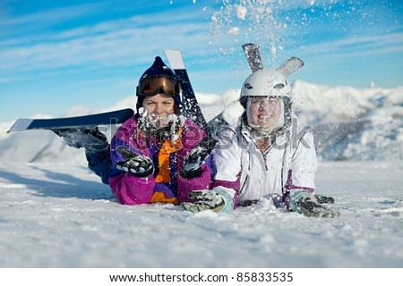 Young female skiers playing in the snow