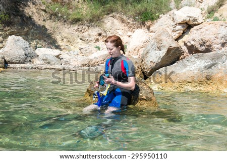 Young female snorkeler sat on a rock in the sea preparing to go snorkeling - stock photo